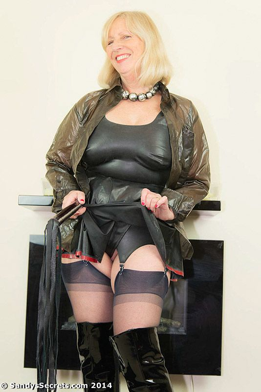 Blonde mature Sandy looks stunning in latex suspenders, nylon stockings and shiny boots